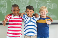 smiling-kids-showing-thumbs-up-in-classr