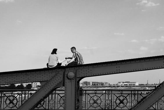 People on a bridge sharing cigarettes, Budapest