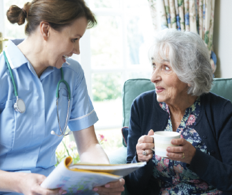 Nurse and older woman converse over coffee