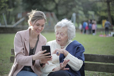 Older woman chats with younger woman on a park bench