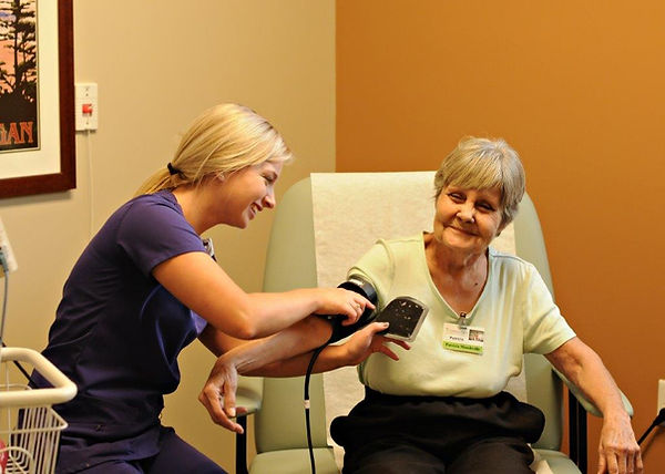 Young medical worker takes an older woman's blood pressure.