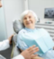 Mulher idosa numa consulta de dentista para coloação de uma prótese dentária