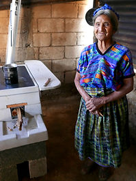 Elderly woman stands beside new ONIL cook stove in Guatemala