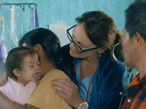 Volunteer nurse comforts baby on service trip in Guatemala