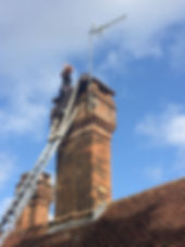 Up a ladder inspecting a chimney