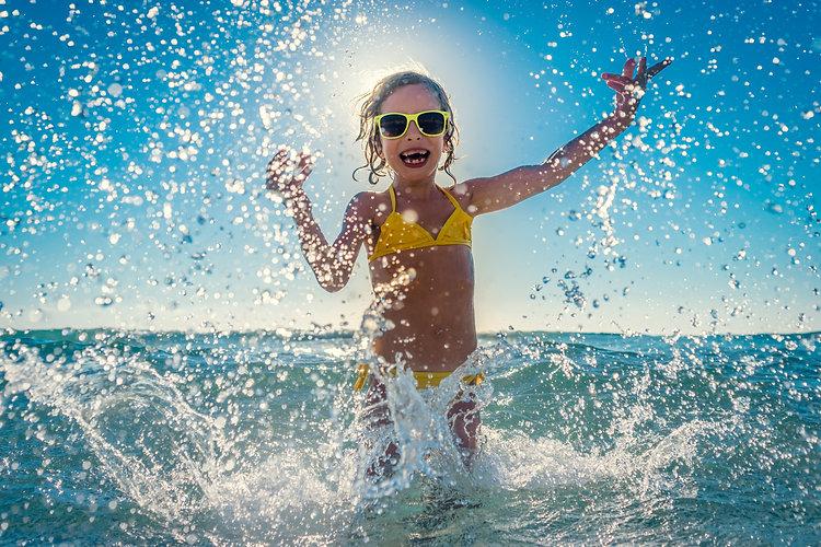 Happy child playing in the sea. Kid havi