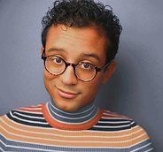 A Latinx non-binary person with short, black curly hair and brown eyes  is centered in the close up photo, in front of a blue grey background. Their shadow is pictured, on the right bottom half of the image. They look directly at the camera, and have a slight smile. They wear brown tortoise shell patterned glasses, and a horizontally striped turtleneck. The turtle neck has white lines in between each stripe, and begins on their neck with a grey blue color, and a light, then dark orange color at the collar. From their shoulders, the color pattern goes dark orange, dark blue, light orange, and light grey blue.