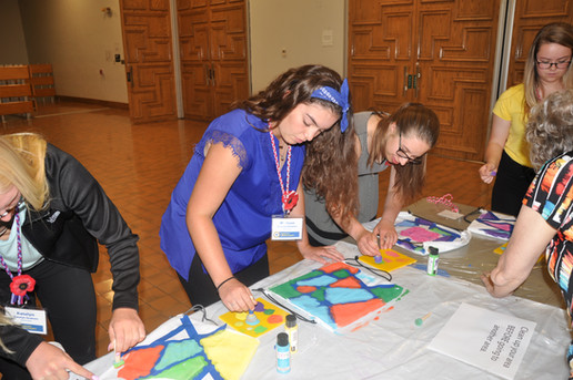 Students painting bags for school supplies.