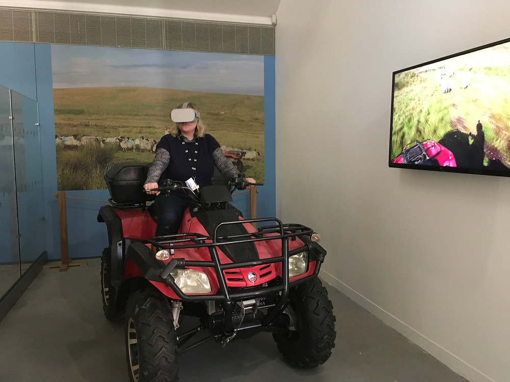 Woman sits on red quad bike with virtual reality headset on