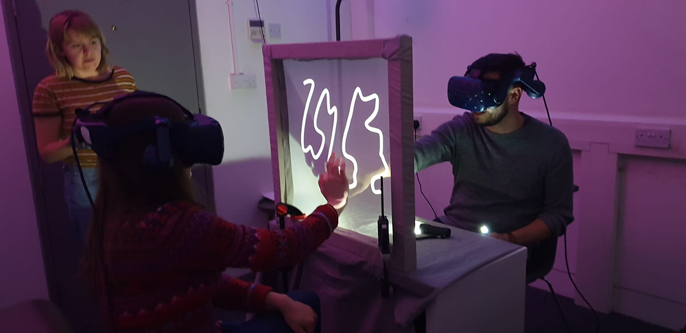 Two people wearing VR headsets reach out and touch a line on a mesh screen