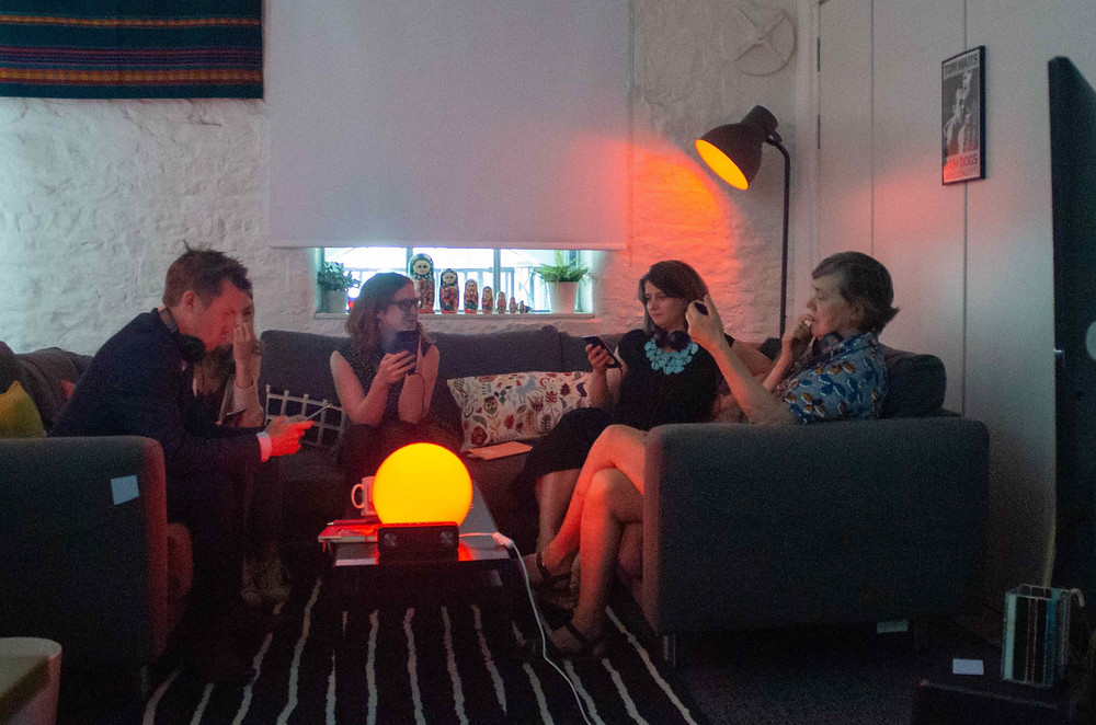 five people sat in a living room space chatting. The lights are set to red