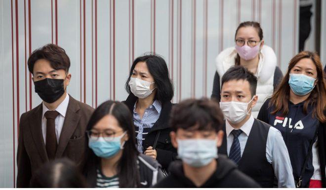 People wearing protective masks walk in Hong Kong's Kwun Tong district