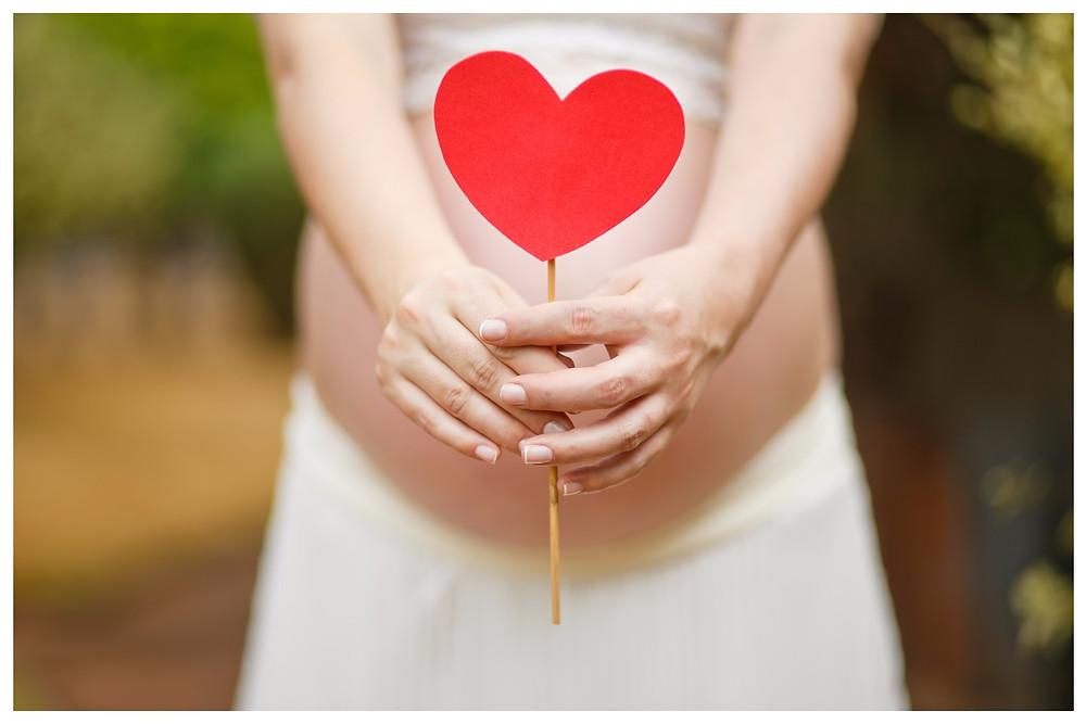 grávida segurando coração