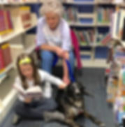 Young girl reading to a therapy dog and it's owner at the Tenafly Public Library