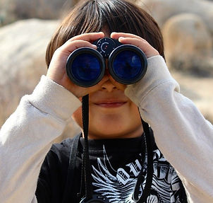 Child viewing the world through binoculars.