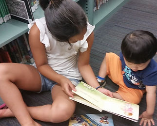 Teen reading a picturebook with a young child at the Tenafly Public Library