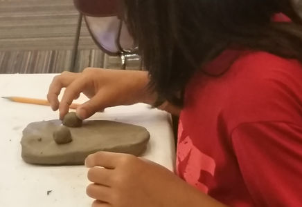 Young child creating a clay mask at a crafting workshop at the Tenafly Public Library.