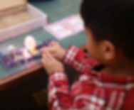 Young boy playing with a Snap Circuit electrical circuit kit at the Tenafy Public Library