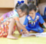 two young children reading  book