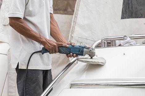 Man buffing a boat using a machine