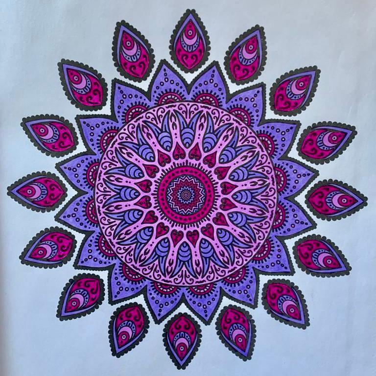 A purple mandala against a light blue background. Work by Sara Castaño.