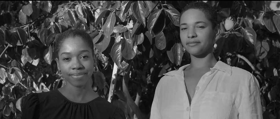 A black-and-white photograph of Chanel Stone and Lucia Olumbunmi Momoh, one clothed in black and the other a white button-up top, stand in front of a persimmon tree staring at the camera.