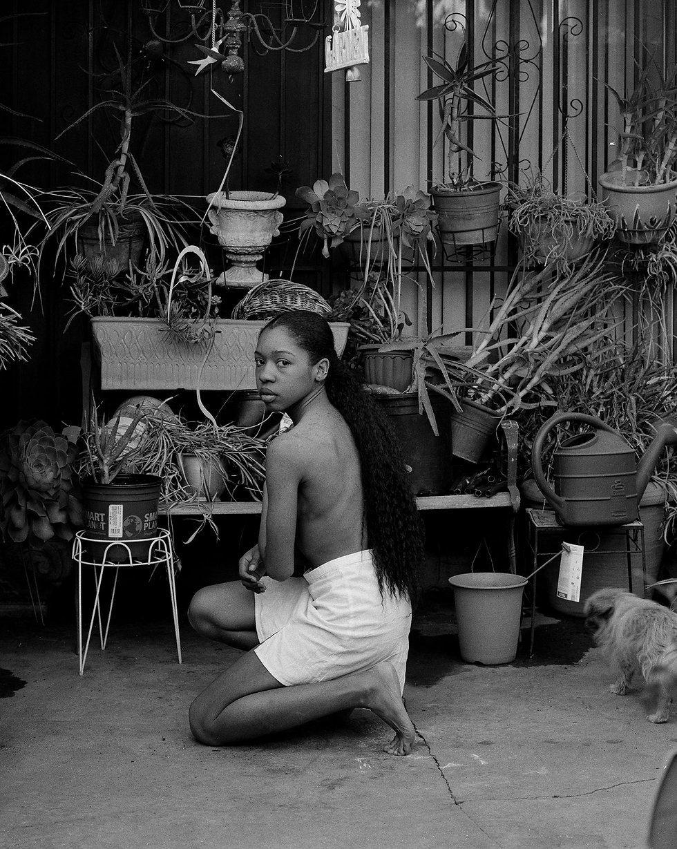 A young Black woman, topless in a white skirt and bare feet, crouches in a small courtyard garden. An array of hung plants, pots, and watering cans form the backdrop. She stares directly at the camera from the center of the frame.
