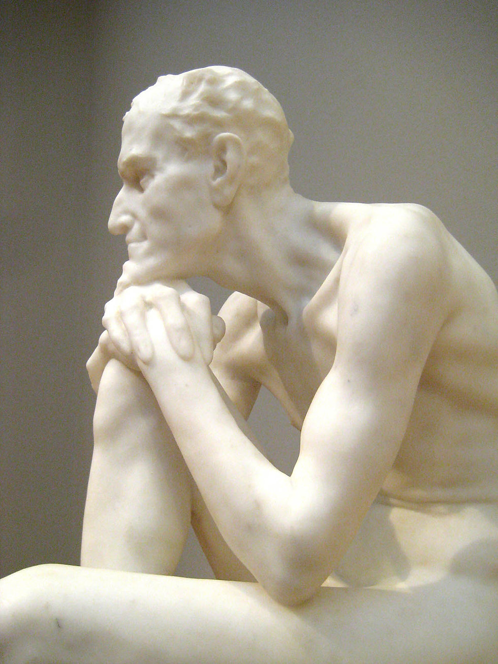 A Greek sculpture of a older man resting his chin on his hands, which rest on one knee.