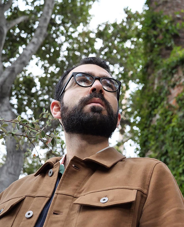 The writer Camilo Garzon looks off to the right. The image is tightly cropped on his shoulders and head, taken from below. A large tree and ivy-covered house are out of focus in the background.