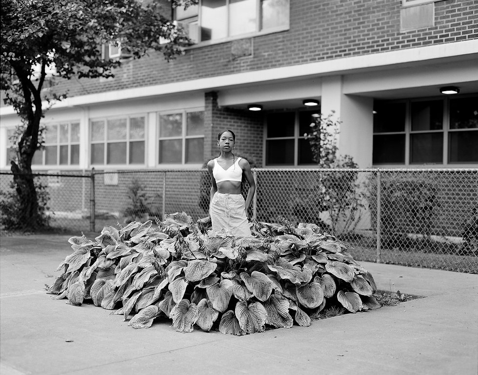 A young Black woman, clothed in a white crop top and white skirt, stands in a lush planter on a Brooklyn sidewalk. She is centered in the frame and stares defiantly back at the viewer.