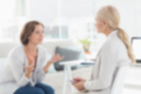 Young woman talking with her therapist i