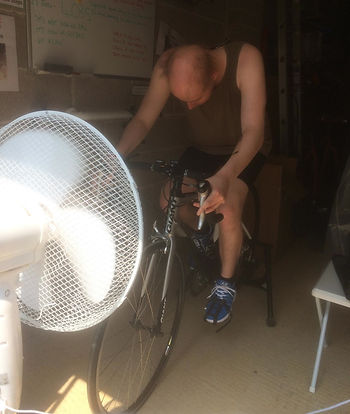 Neil Vines cycling against the head wind of the fan he used to keep cool