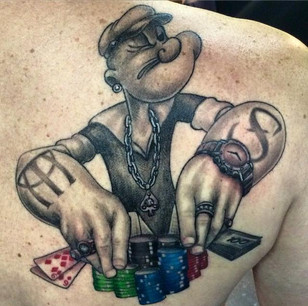 Realistic black and grey shaded shoulder tattoo of Popeeye Gambling.