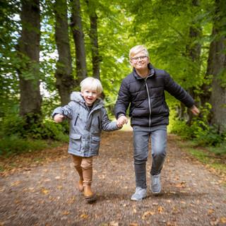 Søskende løber i skoven - familiefotografering.