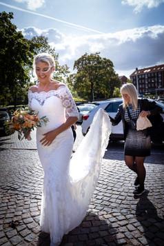 Veninde hjælper bruden ind i kirken i solskinsvejr