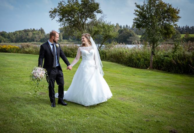 Brudepar ser forelsket på hinanden i det grønne ved sø i nordsjælland