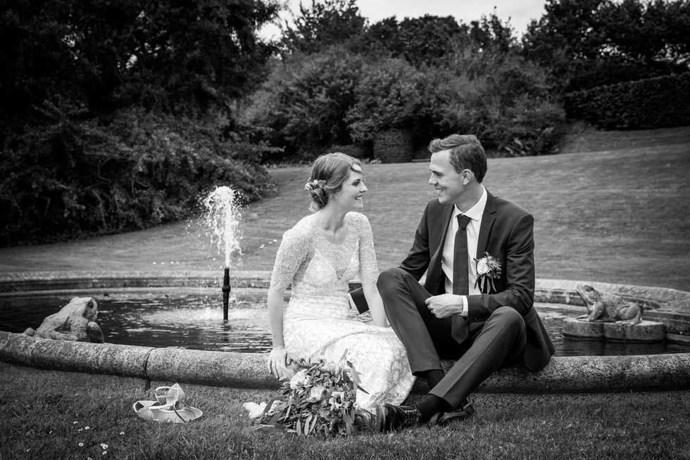 Bryllupsbillede af brudepar ved lille dam i Gisselfeld Slotspark
