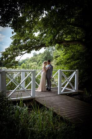 Romantisk billede af brud og brudgom ved hvid bro i Lejre på midtsjælland