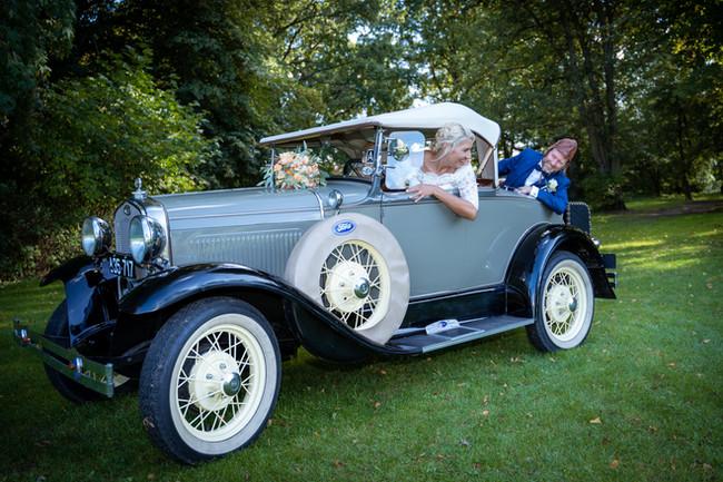 Brudepar har det sjovt i veteranbilen.
