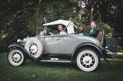 Brudepar har det sjovt ved den gamle veteranbil.