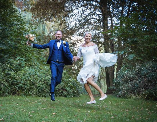 Brudepar hopper glade i det grønne.