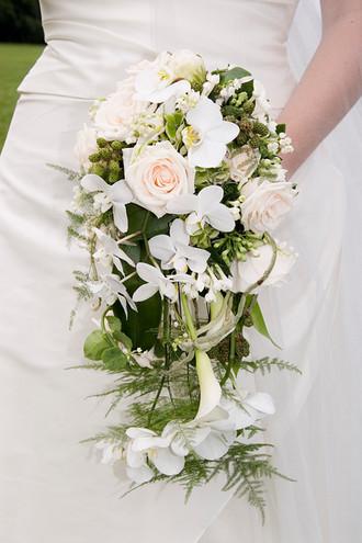 bryllupsfoto af brudebuket med brudekjole som baggrund