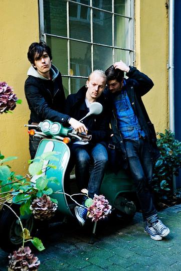bandfoto af The Floor is made of Lava on location med blomster og scooter og gul mur