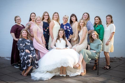 Gruppebillede af brudepiger og gæster med bruden i midten.