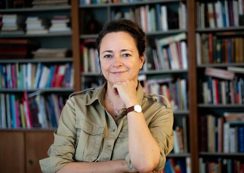 Portræt af erhvervskvinde taget ved bogreol. Kunstner.