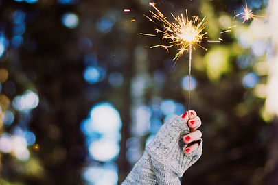 A hand partway covered by a gray sweater sleeve holds up a lit sparkler.