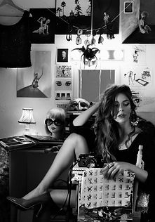 emerging british female artist and photogrpaher in studio, lauren thompson, with gypsy earings curly hair and high heels she is surrounded by props, masks, drawings, postcards, workbooks, costumes and sunglasses
