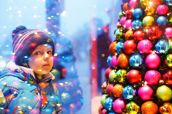 Adorable little boy looking through the display window at Christmas decoration in the shop