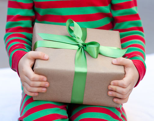 child holding a christmas present nicely wrapped.jpg