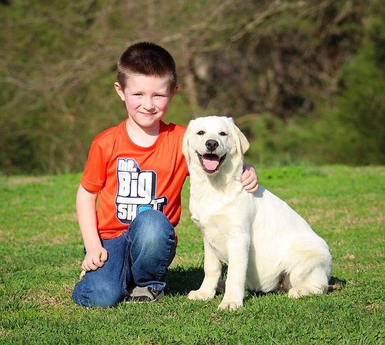 Boy with White Labrador Puppy